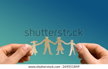 Family. Paper chain family protected in cupped hands - stock photo