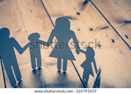 Family paper chain on a wooden background - stock photo