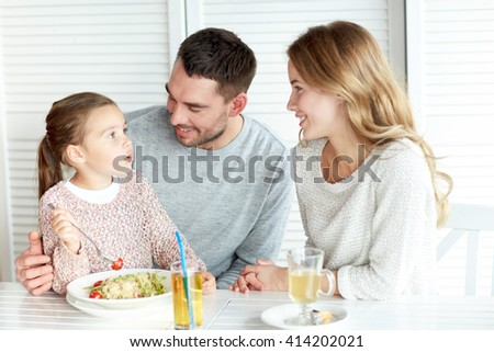 family, parenthood, communication and people concept - happy mother, father and little girl eating pasta for dinner and talking at restaurant or cafe - stock photo