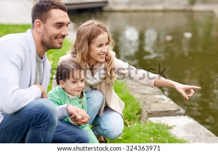 family, parenthood, leisure and people concept - happy mother, father and little girl walking in summer park near pond - stock photo