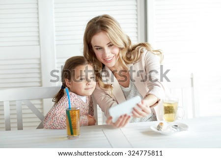 family, parenthood, technology and people concept - happy mother and little girl having dinner and taking selfie by smartphone at restaurant