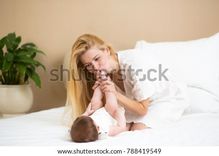 family, parenting morning concept. happy baby with mother in bed at home