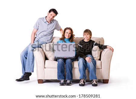 Family: Parents and Son Use Laptop On Couch - stock photo