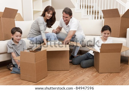 Family, parents, son and daughter, unpacking boxes and moving into a new home. - stock photo