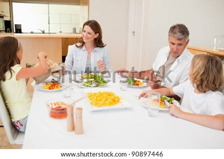 Family passing around the breadbasket during the dinner - stock photo
