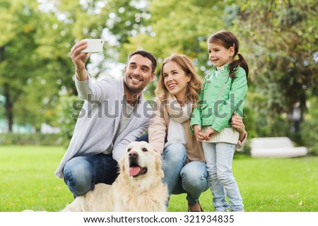 family, pet, animal, technology and people concept - happy family with labrador retriever dog taking selfie by smartphone in park - stock photo