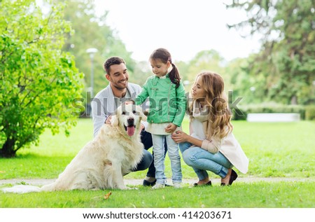 family, pet, domestic animal and people concept - happy family with labrador retriever dog on walk in summer park - stock photo