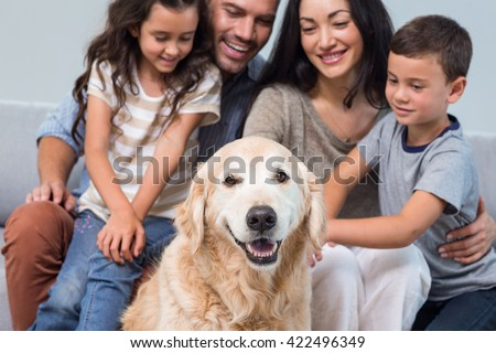 Family petting dog in living room - stock photo