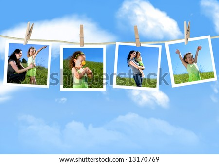 Family photographs hanging on a clothesline against a blue sky - stock photo