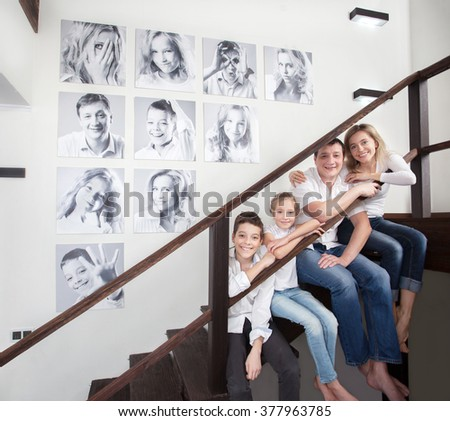 Family photos on the wall. Portraits of family stairwell - stock photo