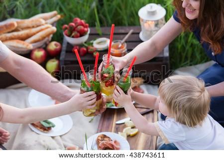 Family picnic. Parents and children clinking glasses bottles of lemonade. - stock photo