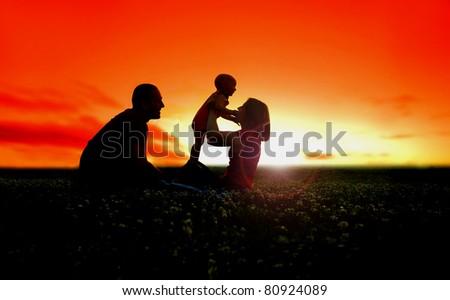 Family picnic sunset flare - stock photo