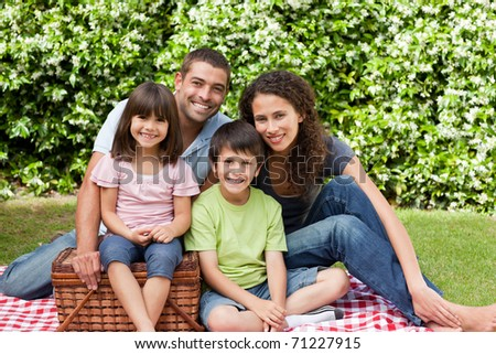 Family picnicking in the garden - stock photo