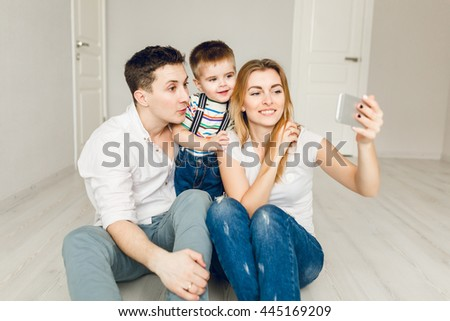 Family picture of two young parents playing with their boy child. They sit on the floor and the kid is between his parents. They wear white t-shirt and jeans. Mom takes a selfie on the smartphone. - stock photo