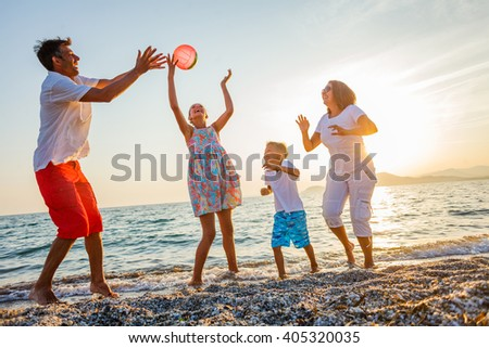 Family play on beach - stock photo