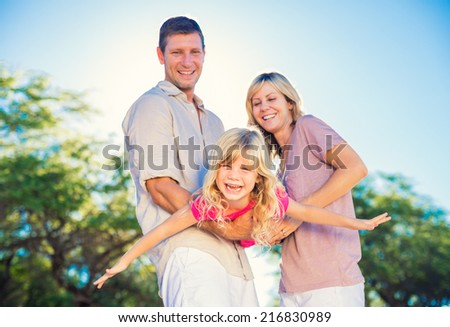 Family Playing Airplane with Young Daughter on the Beach - stock photo