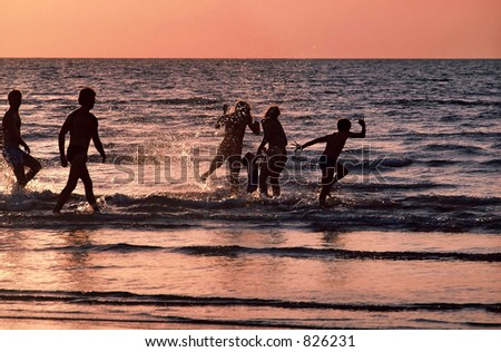 Family playing at the beach at Sunset