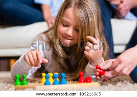Family playing board game ludo at home on the floor, close up on child - stock photo