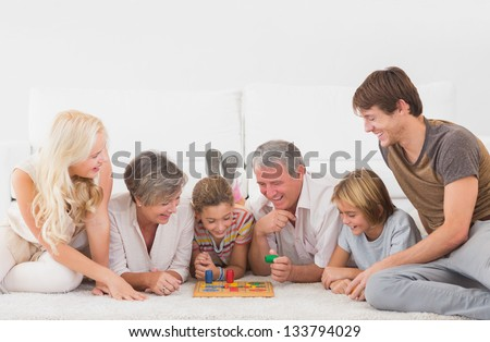 Family playing board games in sitting room - stock photo
