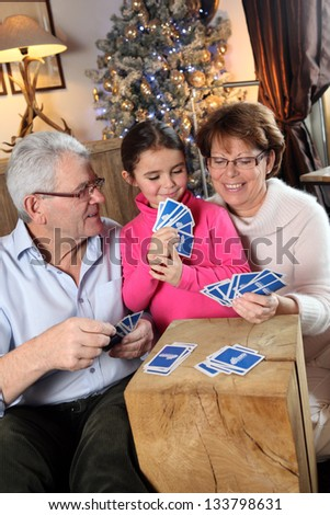 Family playing card game at Christmas - stock photo