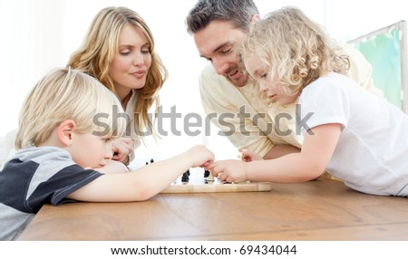Family playing chess on a table at home - stock photo