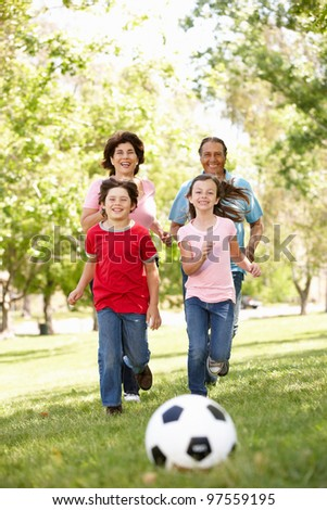 Family playing football in park - stock photo