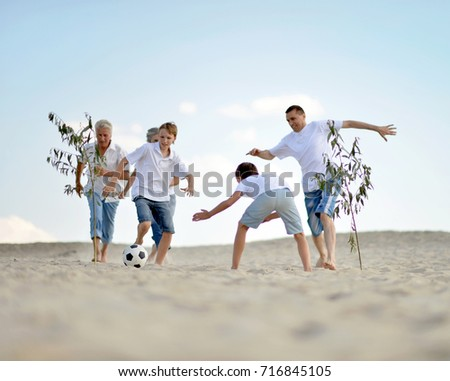 Family playing football on a beach