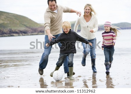 Family playing football on beach - stock photo