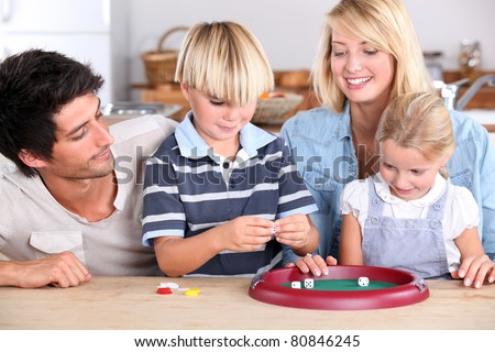 Family playing game at kitchen table - stock photo