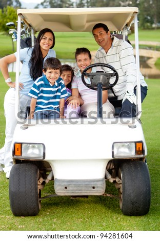 Family playing golf and riding a cart though the course - stock photo