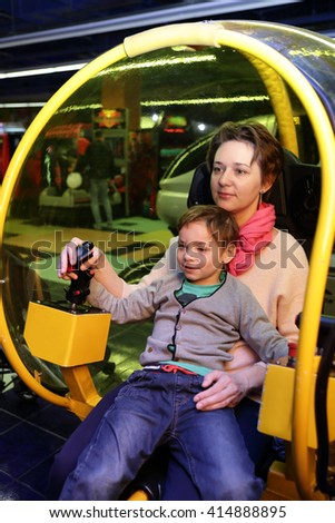 Family playing helicopter simulator in an amusement park - stock photo