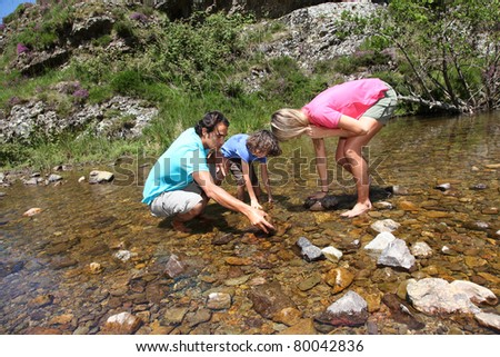 Family playing in river with peebles - stock photo