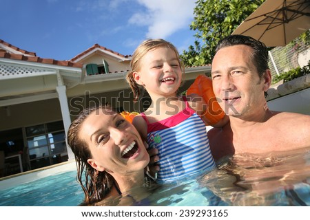 Family playing in swimming pool of private villa - stock photo