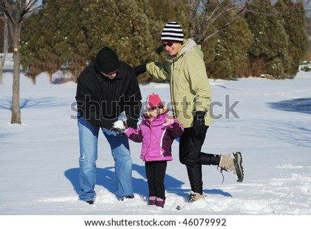 family playing in the snow - stock photo