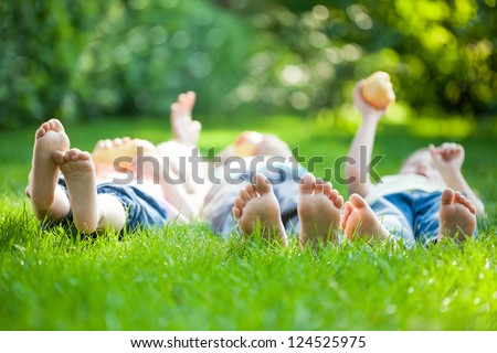 Family playing on green grass in spring park