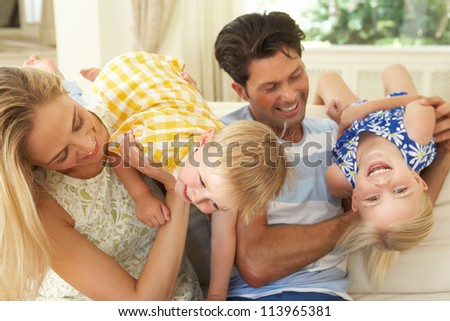 Family Playing On Sofa At Home
