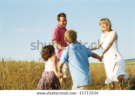 Family playing outdoors smiling - stock photo