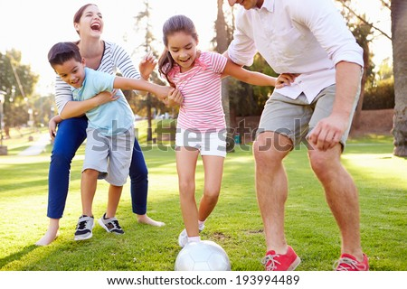 Family Playing Soccer In Park Together - stock photo
