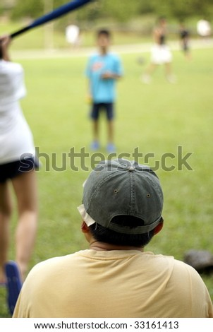 Family playing softball together, focus on father wearing cap