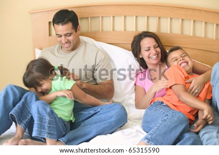 Family playing together on bed - stock photo
