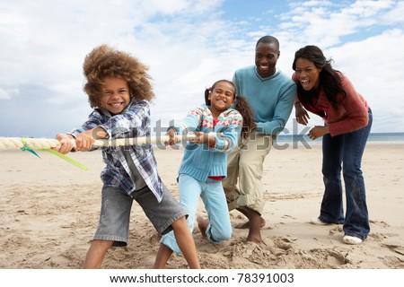 Family playing tug of war on beach - stock photo