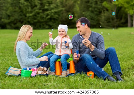 Family playing with bubbles outdoors. - stock photo
