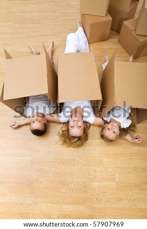 Family playing with carboard boxes in their new home - stock photo