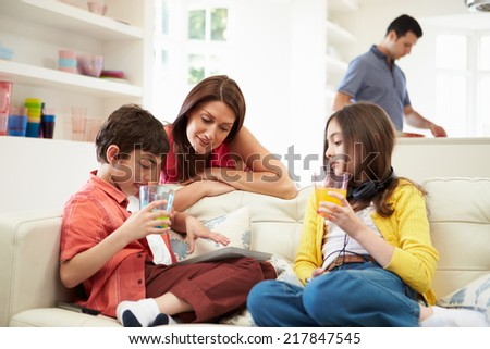 Family Playing With Digital Tablet And MP3 Player - stock photo