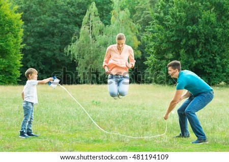 Family Playing With Jump Rope In The Park
