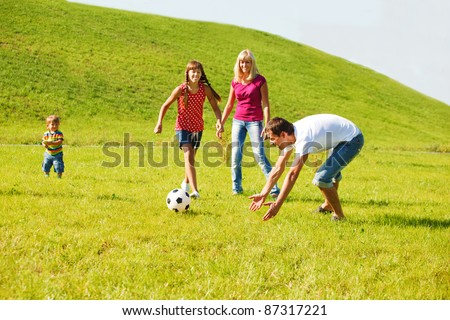 Family playing with the ball in summer park - stock photo