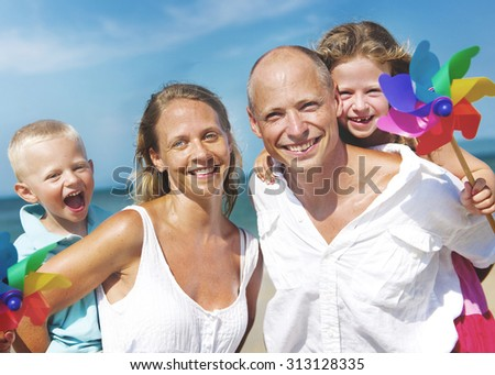 Family playing with windmill on beach Concept