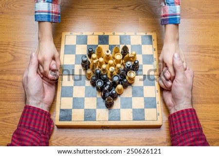 Family playing wooden chess pieces - stock photo