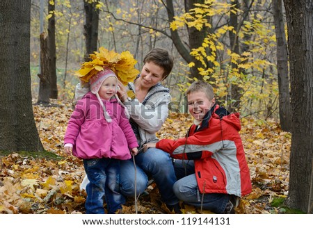 family plays in the autumn woods - stock photo