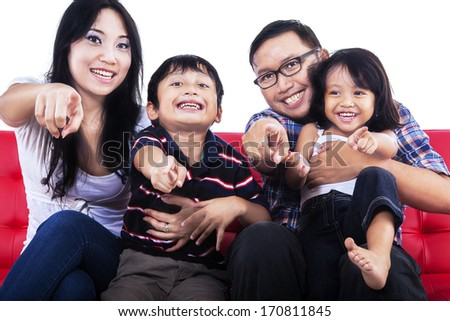 Family pointing at you and sitting on red sofa - stock photo